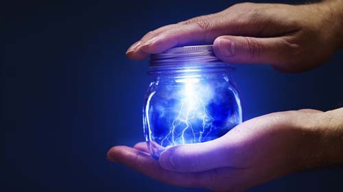 16438851 - conceptual image of a man holding a jar with lightnings in his hands.